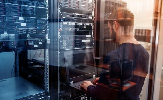 Man using laptop in network server room